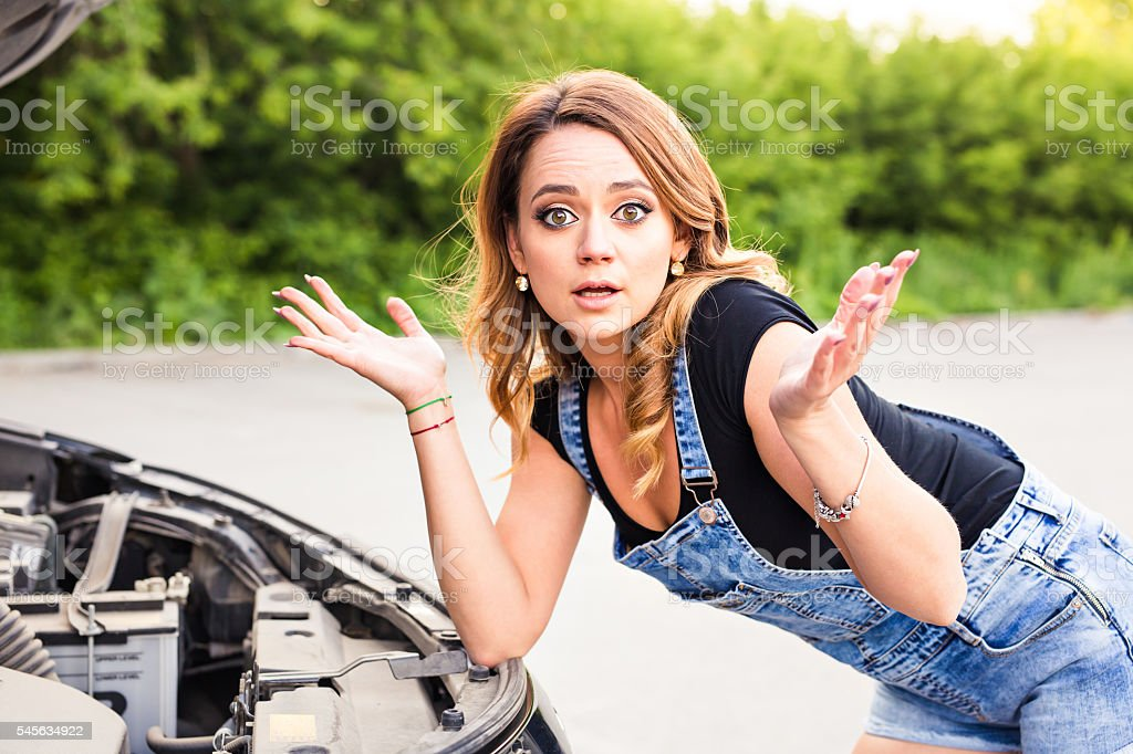 Feeling confusion. Portrait of embarrassed young woman with broken car. stock photo