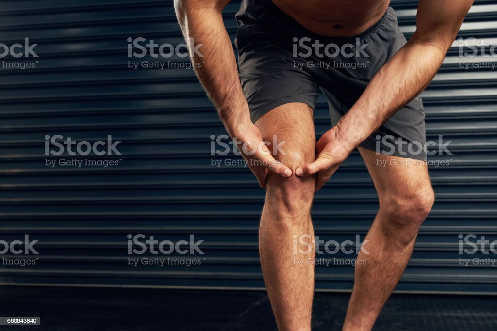 Feeling the pain in his knee stock photo