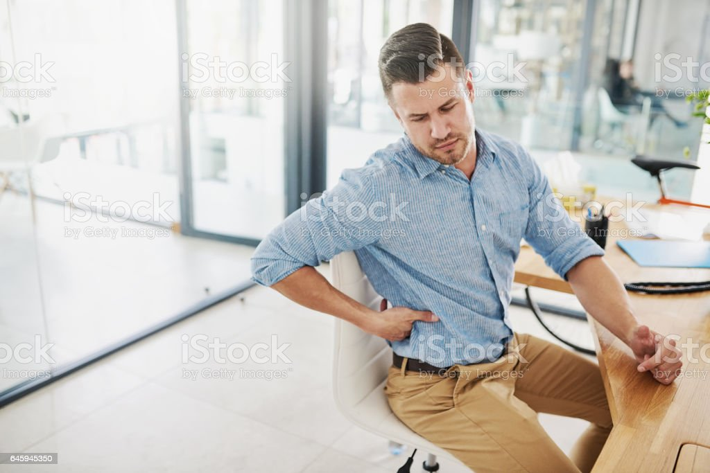 Feeling the strain of a long day at his desk stock photo