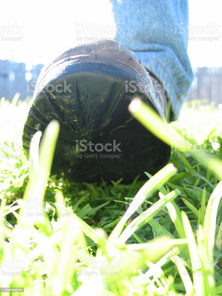 feet - about to crush the grass stock photo
