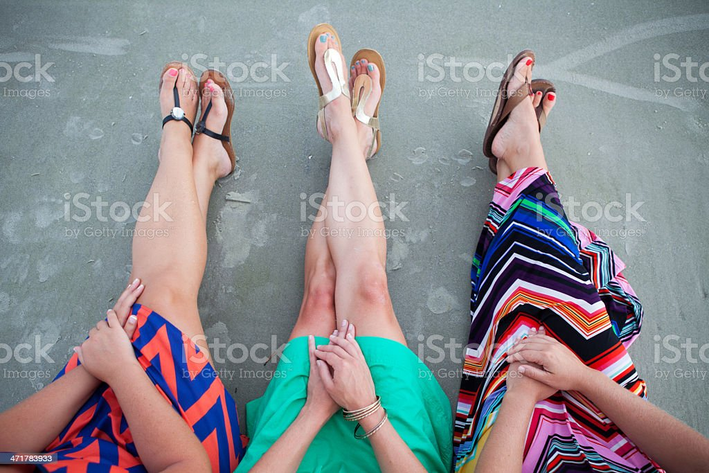 Feet and legs of three friends sitting on the beach royalty-free stock photo