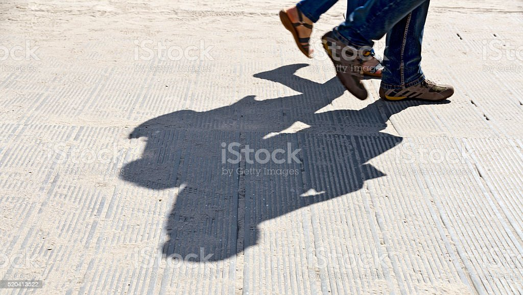 feet and shadow of two walkers stock photo
