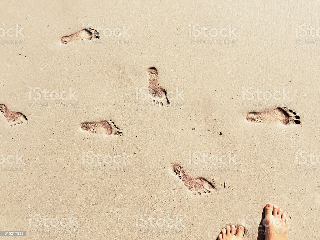 Feet and steps marks on the white sunny sand beach stock photo