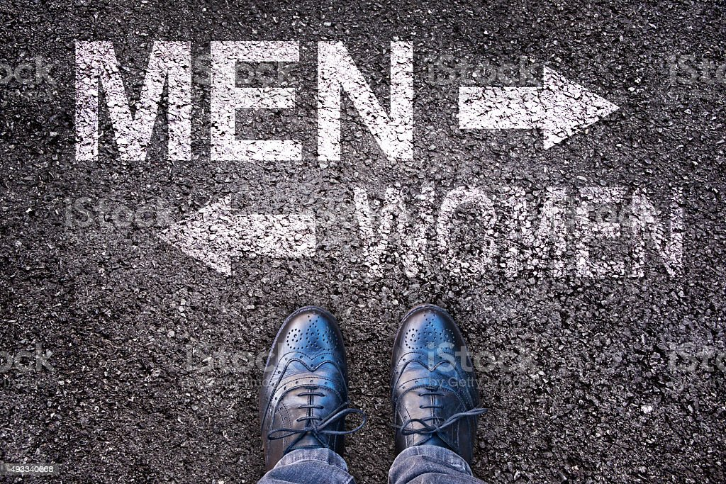 Feet and words men and women painted on a road stock photo