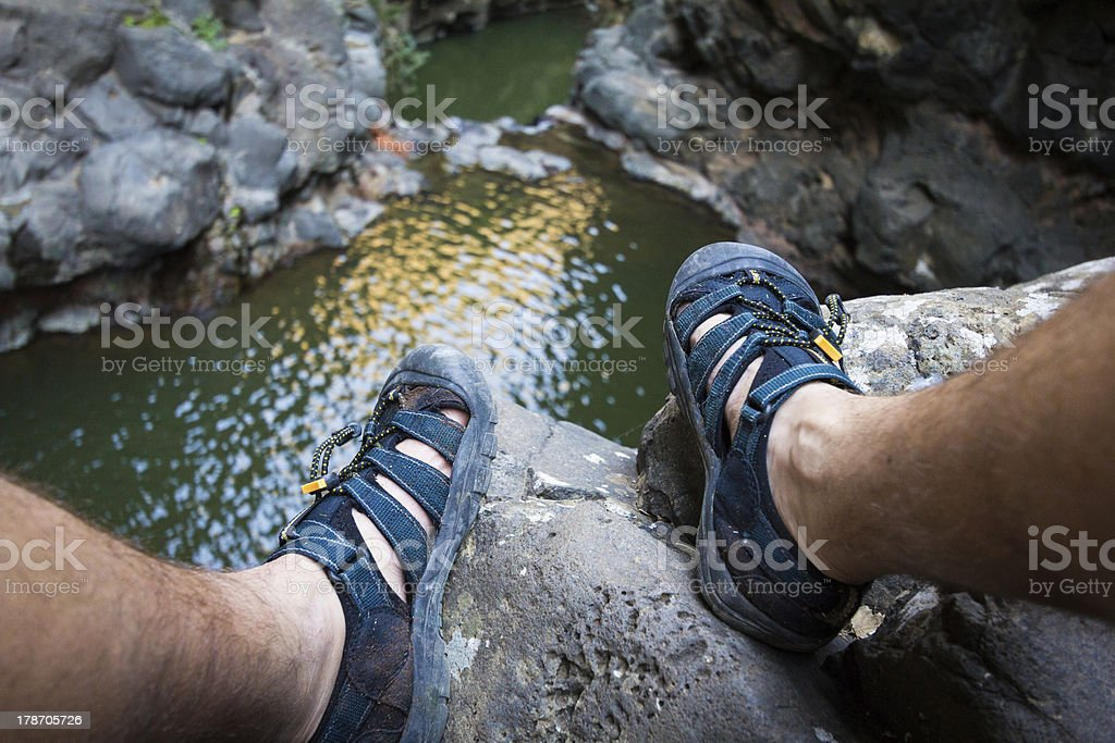 Feet blue sandals closeup cliff stone. royalty-free stock photo