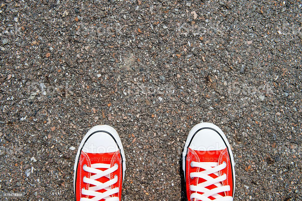 Feet concept with red sneakers on black background stock photo