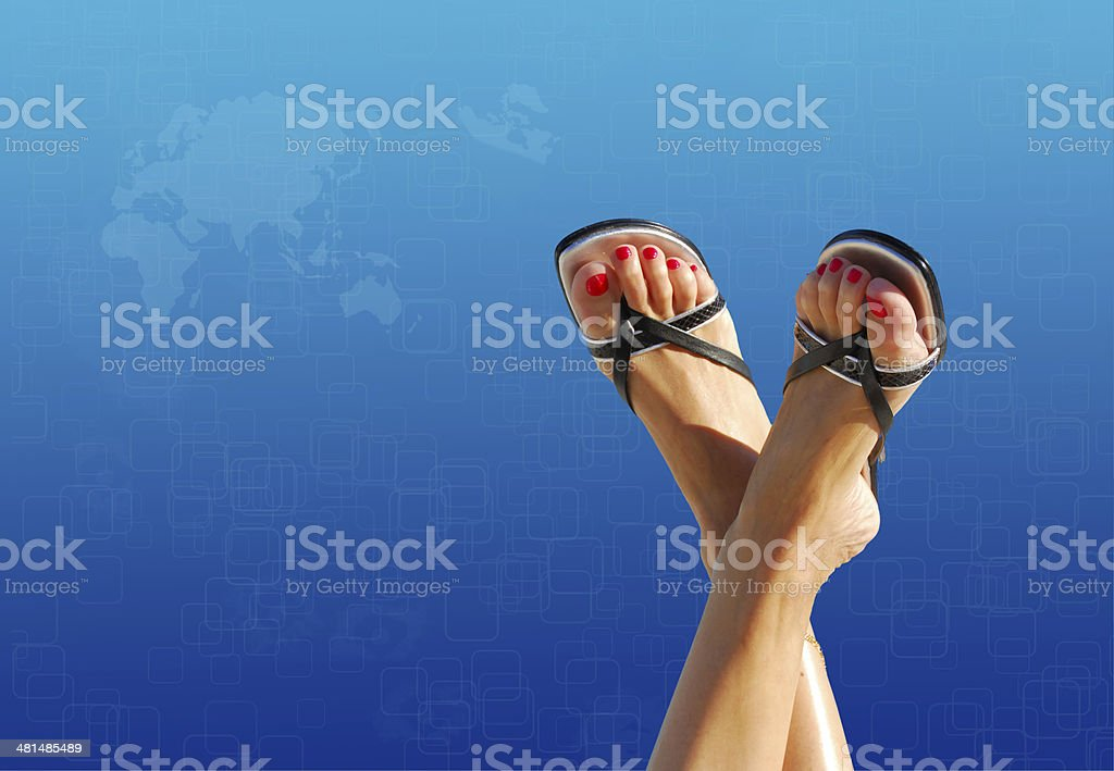 feet crossed with blue world map in background royalty-free stock photo