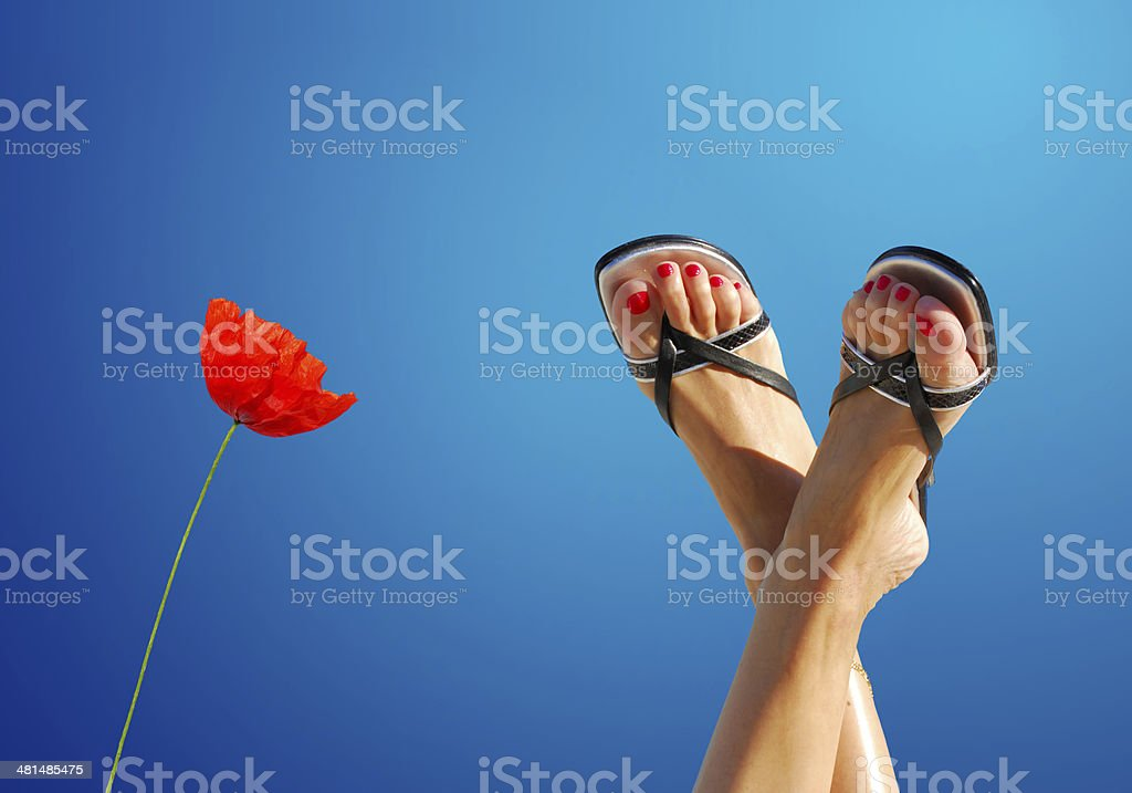 feet crossed with poppy symbolizing wellbeing royalty-free stock photo