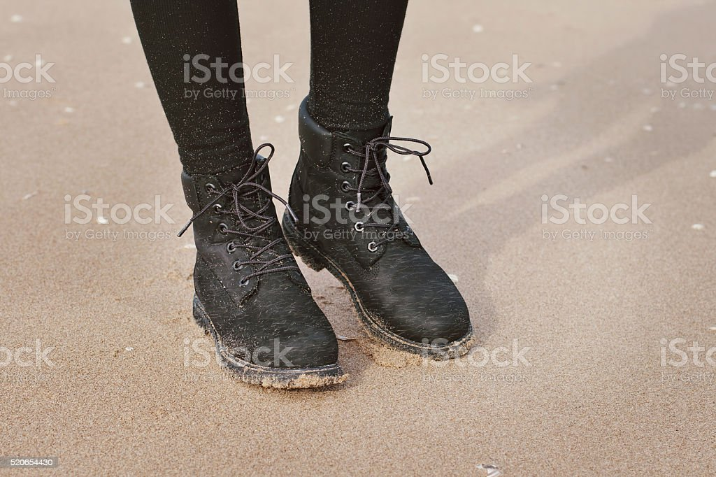Feet in black boots close-up stock photo