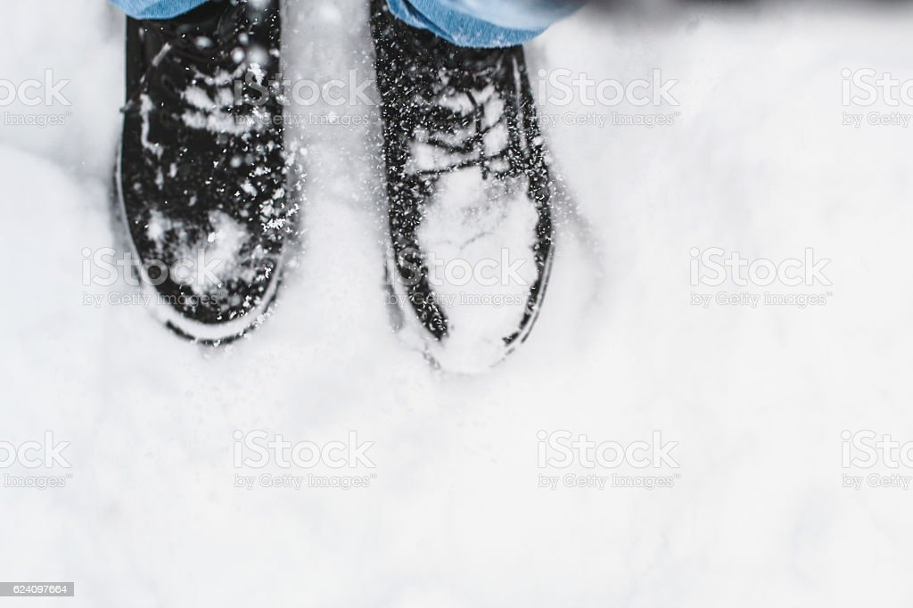 Feet in black boots under snowfall close up, copy space. stock photo