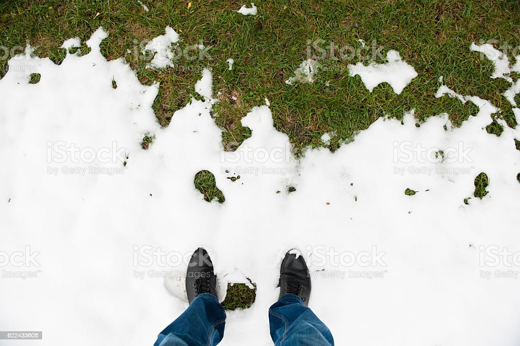 feet in   boots  in snow in front of green grass stock photo