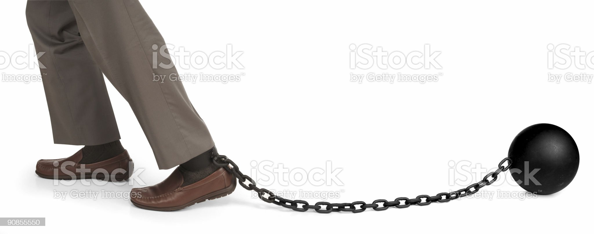 Feet in brown shoes hauling a ball and chain royalty-free stock photo