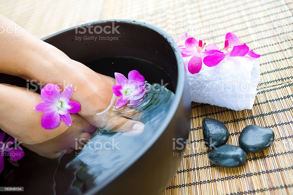 feet in foot spa bowl with orchids royalty-free stock photo