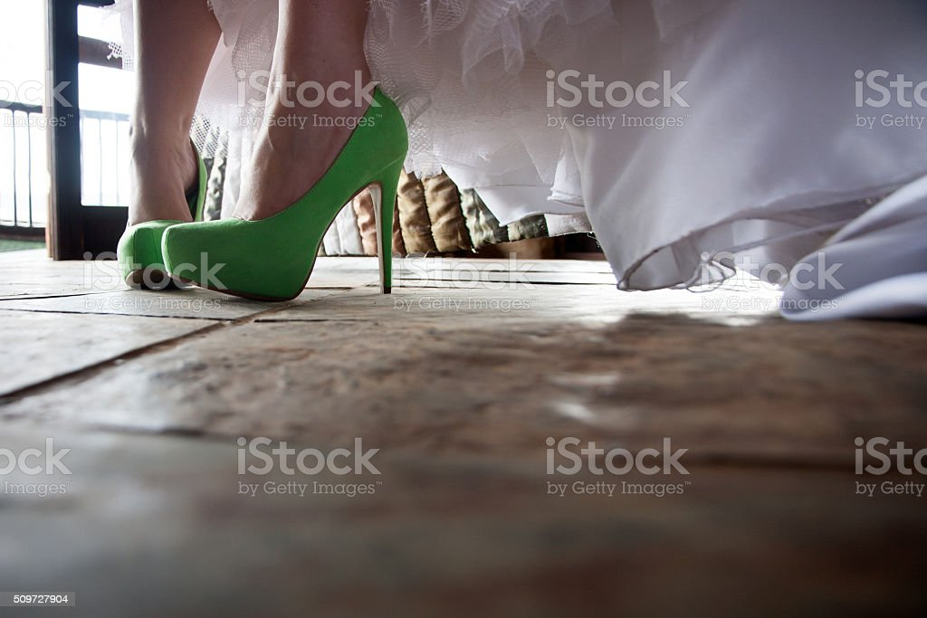 Feet in green stiletto's and wedding dress 1 stock photo