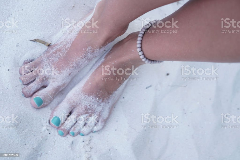 Feet in sand, Maldives stock photo