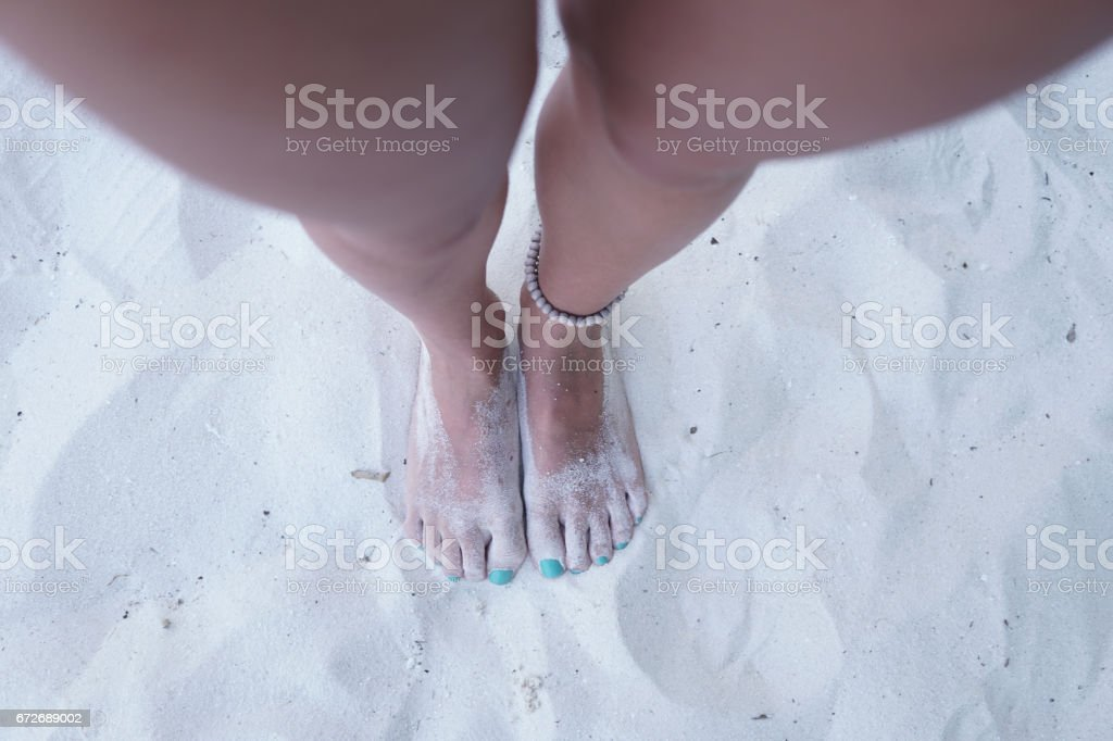 Feet in sand, Maldives stock photo