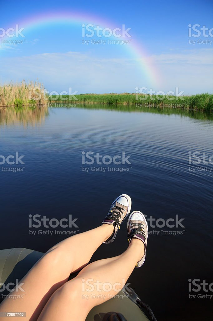 Feet in sneakers on river landscape with rainbow stock photo