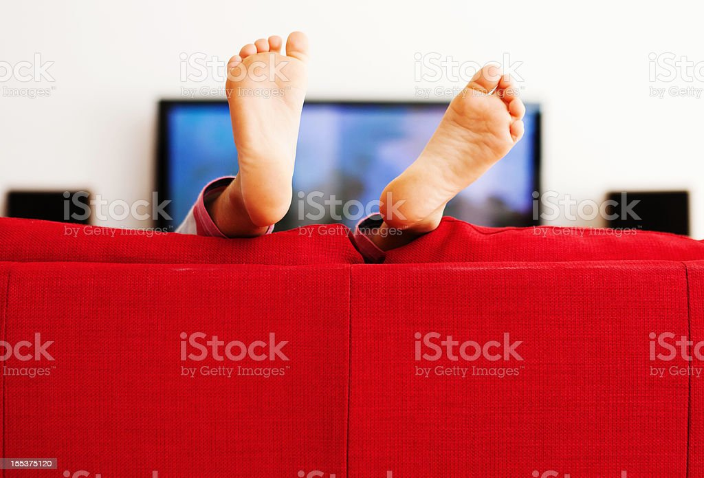 Feet in the air as little boy plays on sofa royalty-free stock photo