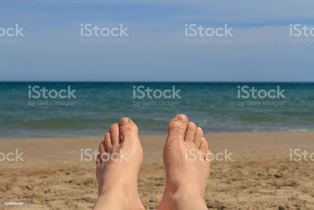 Feet in the sand on the beach. In the background is the sea. stock photo
