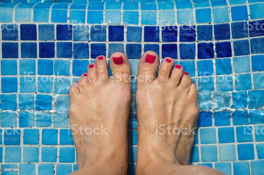 Feet in the swimming pool. stock photo