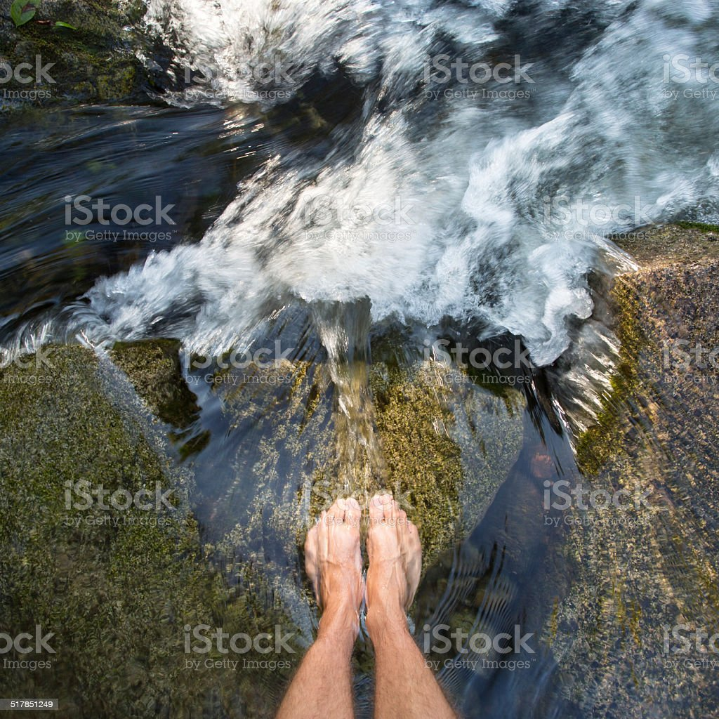 feet in waterfall stock photo