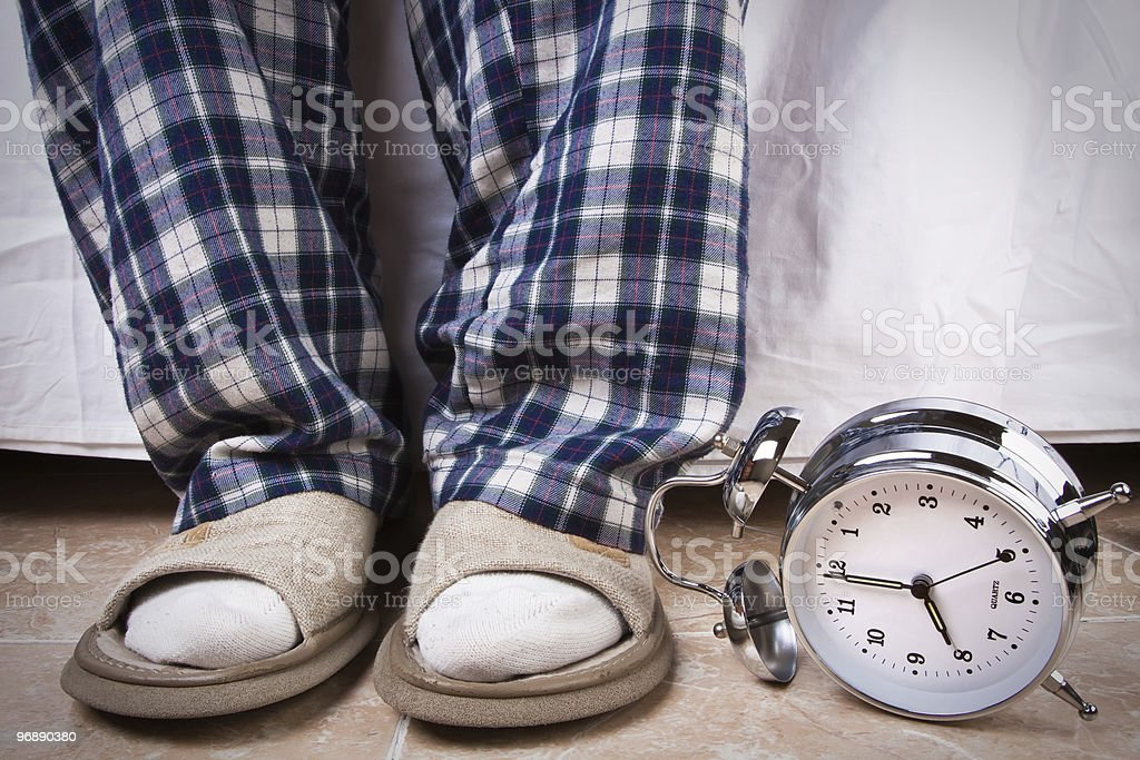 Feet just got out of bed, alarm at 8am has fallen down stock photo