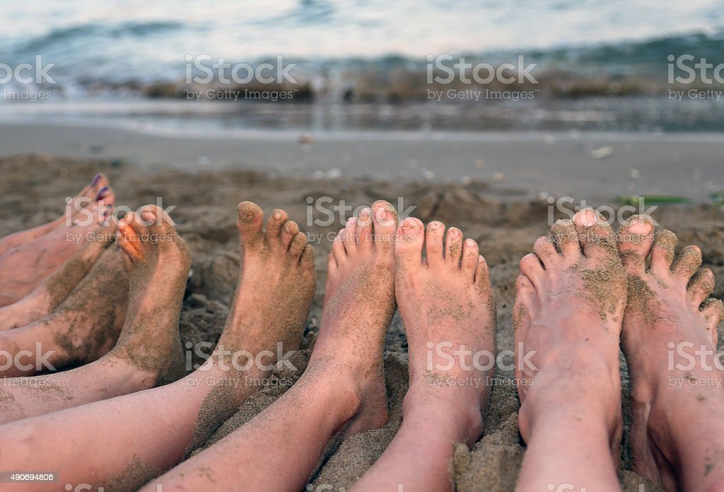 feet of a family barefoot by the sea stock photo