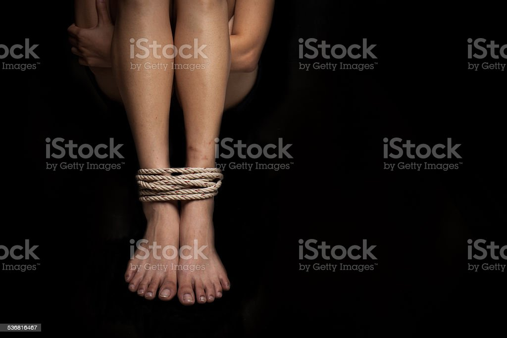 Feet of a missing kidnapped, abused, hostage, victim woman tied stock photo