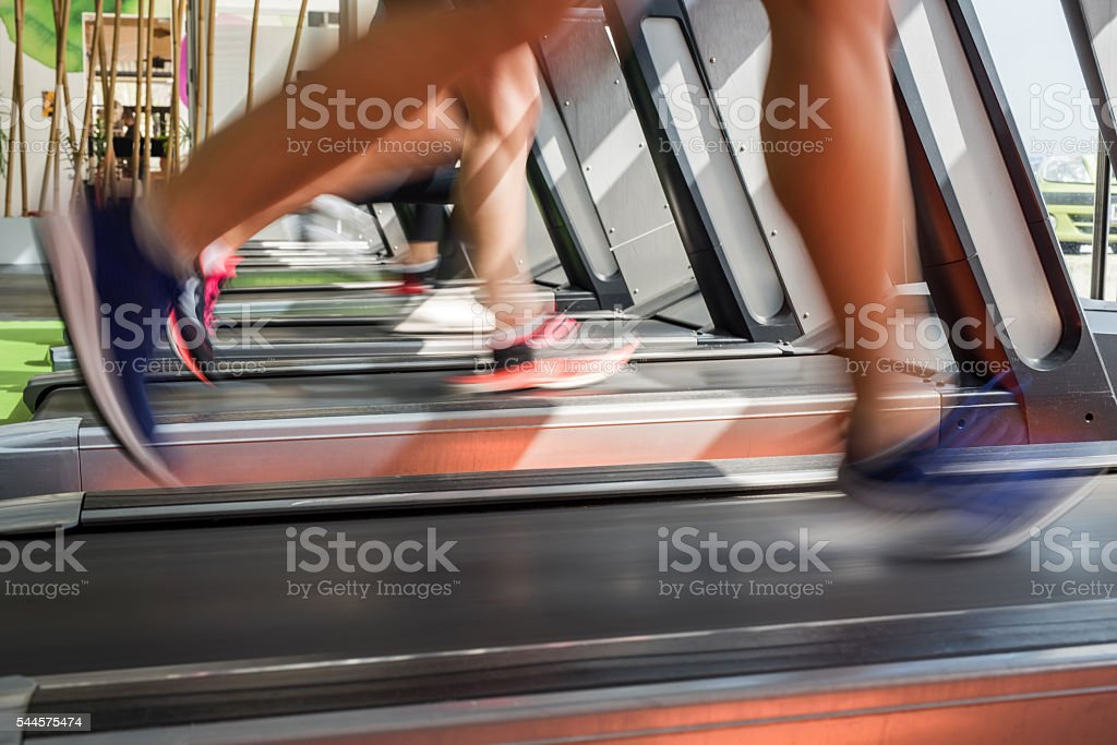 Feet of a runners in blurred motion jogging on treadmill. stock photo