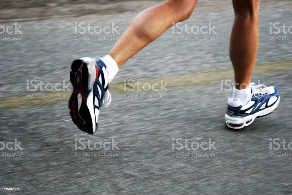 Feet of a running woman on asphalt next to faded yellow line stock photo