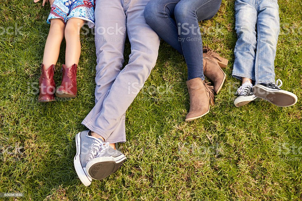 Feet of a young family lying on grass in a park, crop stock photo