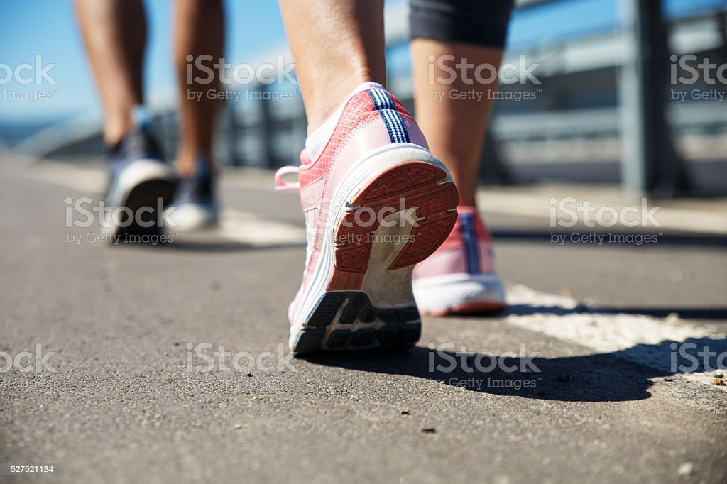 Feet of an athlete couple running on a pathway stock photo