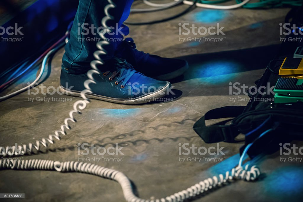 Feet of bass guitar player on a stage stock photo