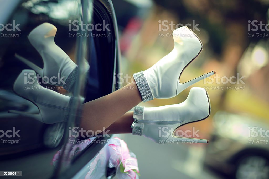 feet of bride peek out from the window of car stock photo
