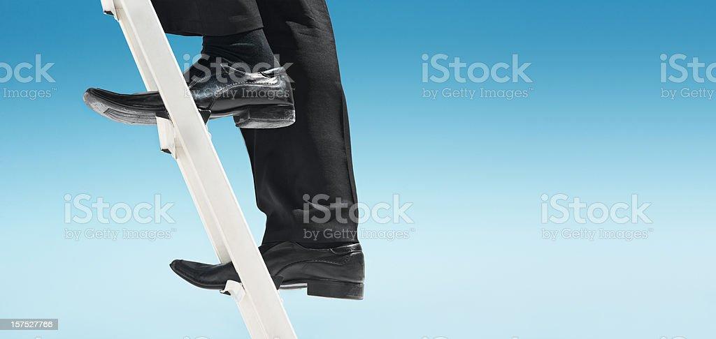 Feet of businessman climbing ladder stock photo