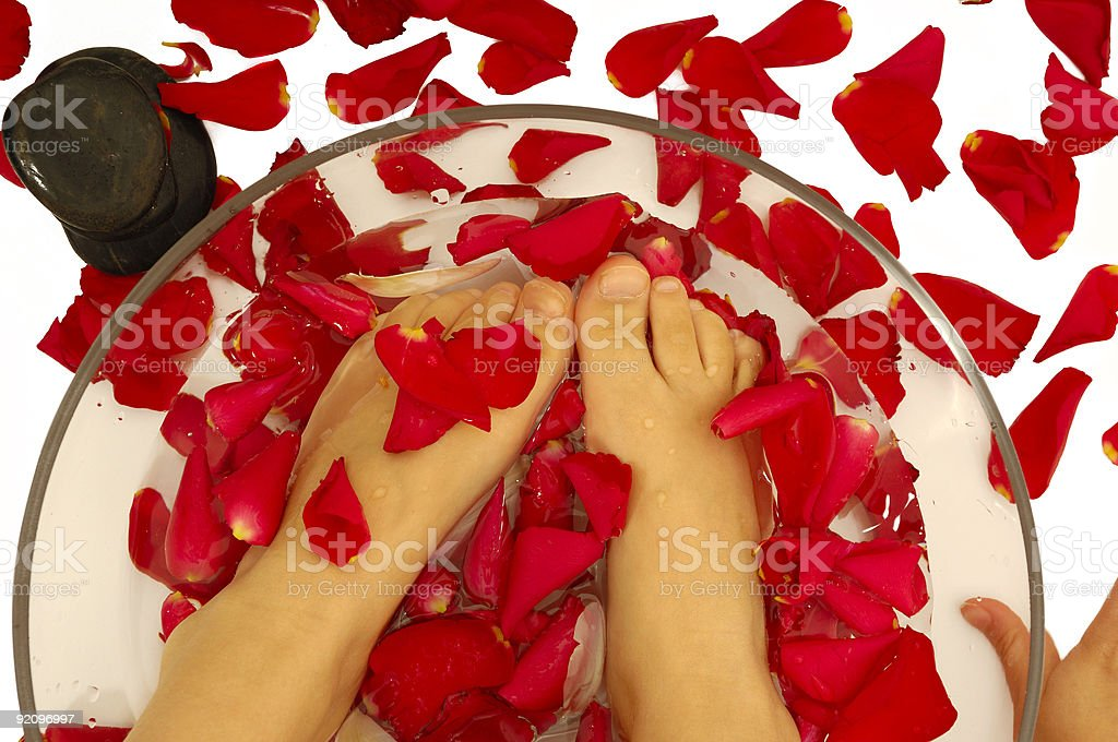 Feet of child in spa with rose petals and stone royalty-free stock photo