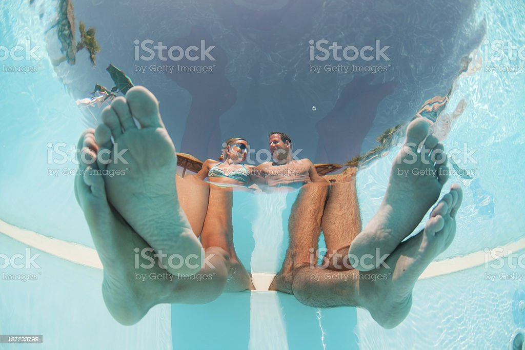 feet of couple in swimming pool stock photo