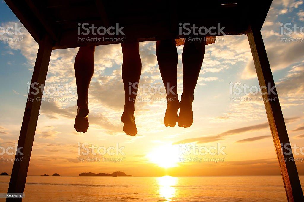 feet of couple sitting on the pier, beach stock photo