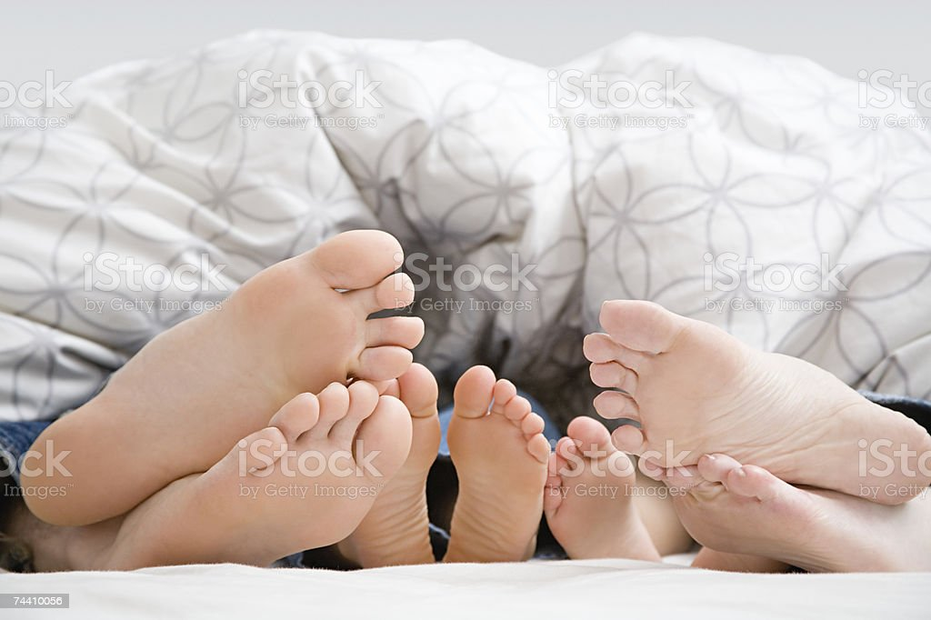 Feet of family in bed royalty-free stock photo