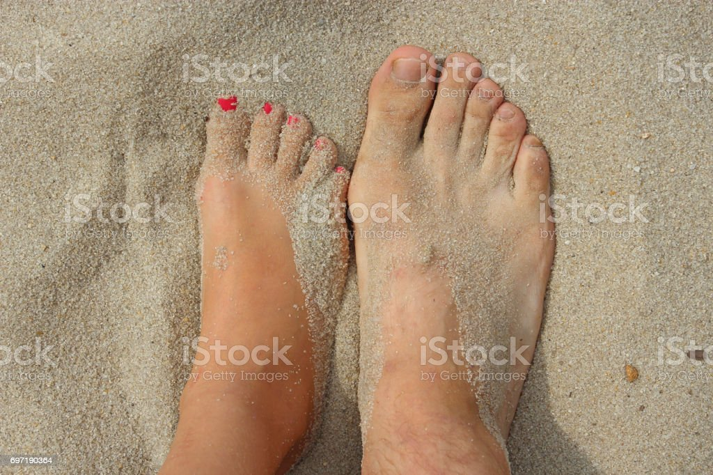 feet of father and his teen daughter on the sand stock photo