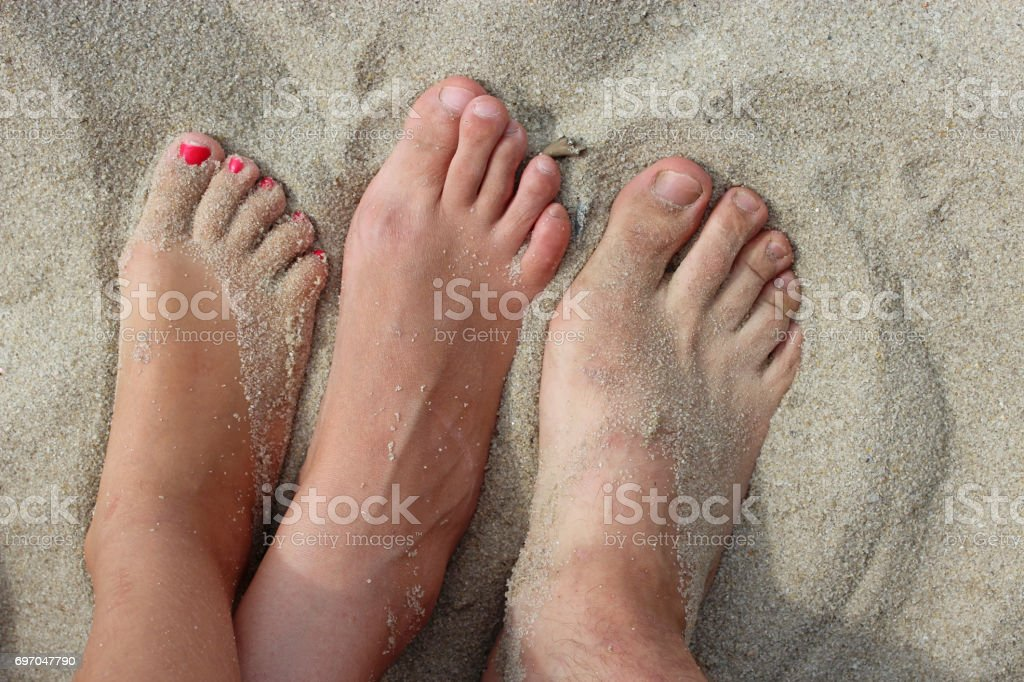 feet of father mother and daughter on the sand stock photo