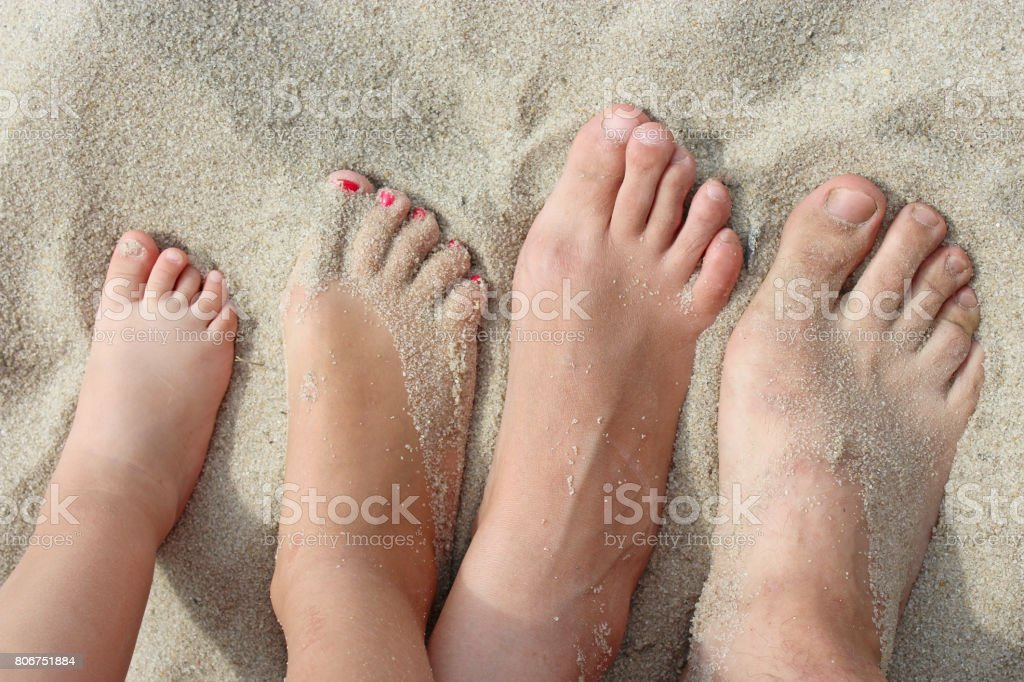 feet of father mother and their daughters on beach sand stock photo