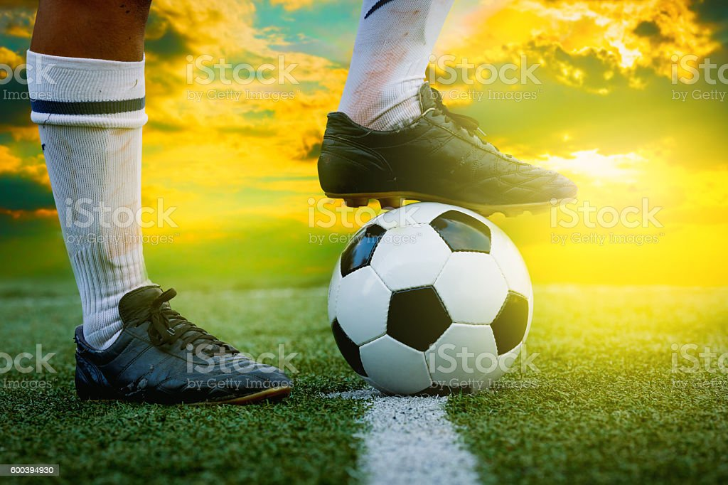 feet of football player tread on soccer ball stock photo