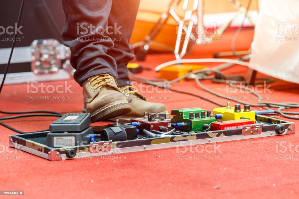 Feet of guitar player on a stage with set of distortion effect pedals. Selective focus stock photo
