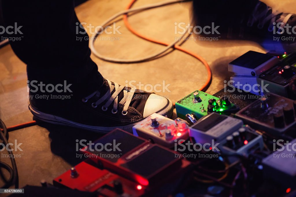 Feet of guitar player with set of effect pedals stock photo