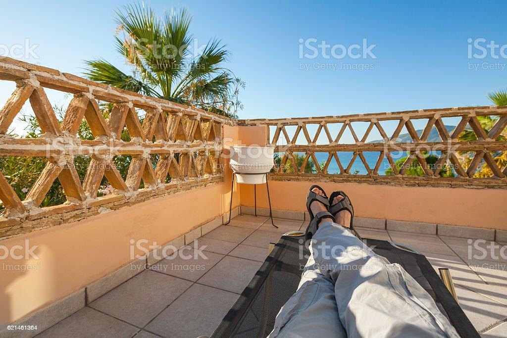 Feet of man relaxing on sun lounger stock photo
