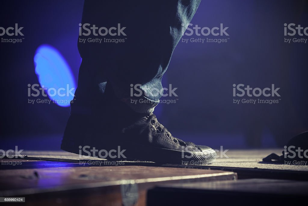 Feet of musican in black sneakers stock photo