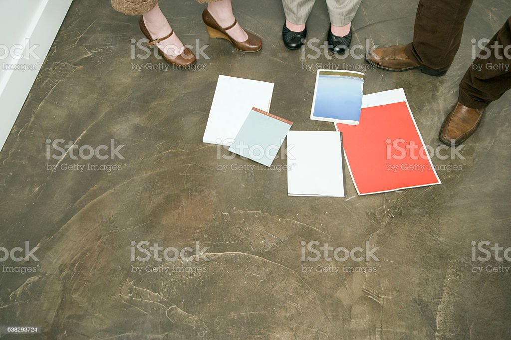 Feet of office coworkers looking at layouts on floor stock photo
