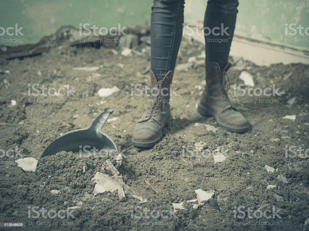 Feet of person by dustpan and dirt stock photo