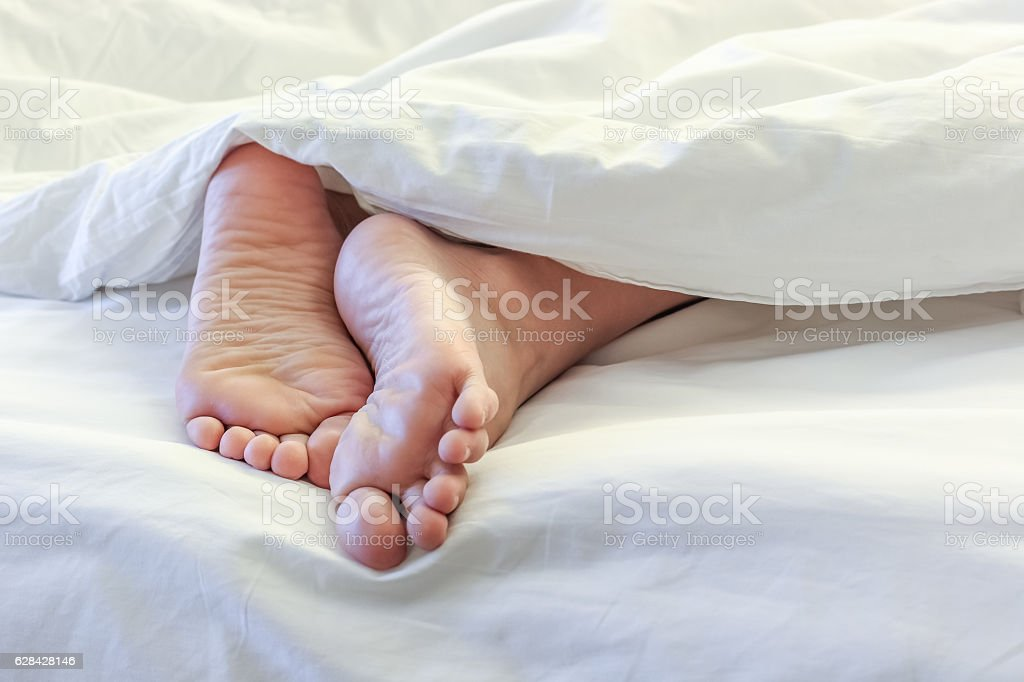 Feet of sleeping woman in white bed room stock photo